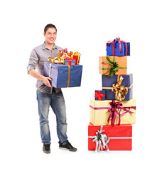 Boy holding a gift next to a pile of gifts