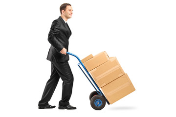 Businessman pushing a hand truck full with cardboard boxes