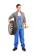 Full length portrait of a mechanic holding a spare tire and hold