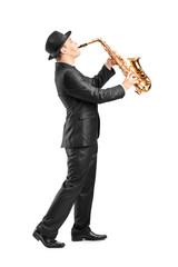 Full length portrait of a man in a suit playing on saxophone