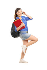 Smiling school girl holding books and talking on a phone