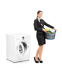 Smiling woman holding a laundry basket next to a washing machine