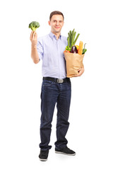 Man holding a shopping bag with products and a broccoli in his h