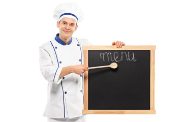 Portrait of a smiling chef pointing on a board