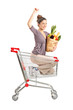 Happy female with a paper bag posing in a shopping chart