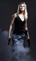 Sexy woman holding gun with smoke