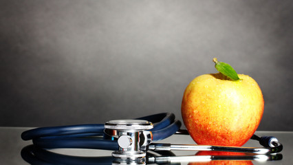 Medical stethoscope and apple on grey