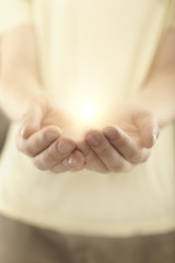 Male hands holding rays of glowing light