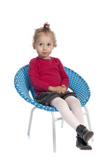 cute little girl sitting in a round blue chair