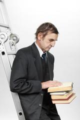 Пожилой мужчина держит в руках старые книги.