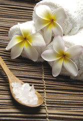 frangipani and roller towel with salt in spoon on  mat