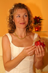Frau packt ein Geschenk aus