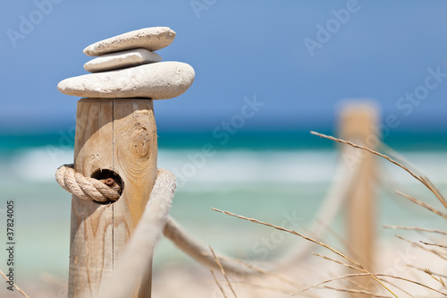 Stones balanced on wooden banister near the beach. © el lobo