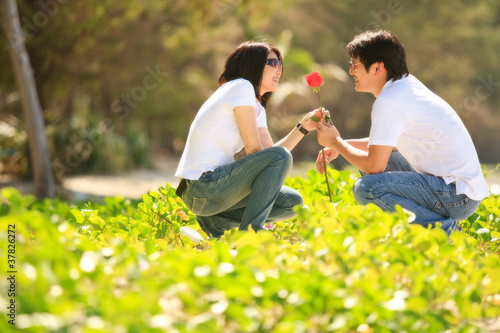 attractive young boy giving beautiful rose to his pretty girlfri