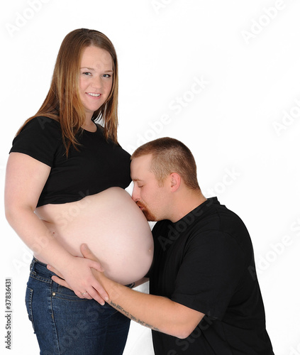 kneeling man kissing his pregnant wifes bare belly. isolated on