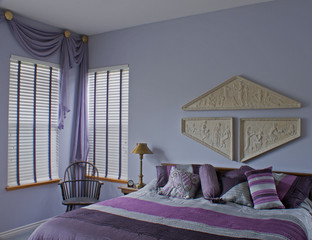 Purple bedroom drapes chair bed windows.