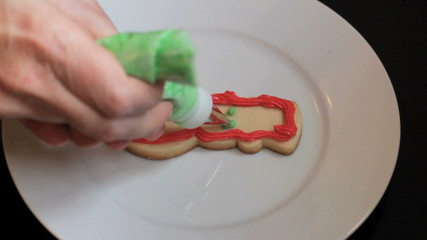 Decorating Snowman Shaped Christmas Cookie With Green Icing