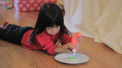 Girl Decorating Christmas Cookie With Red Icing