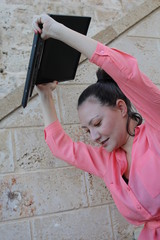 A woman is raising a laptop in order to break it, outdoor