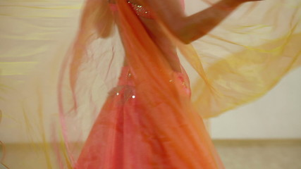 Belly of the woman dancing in the orange dancing dress