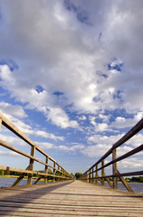 Long wooden plank bridge over lake and cloudy sky.