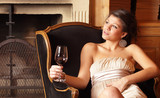 woman with a glass of red wine at a fireplace