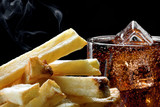 Deep-fried potatoes and cold cola with ice, black background