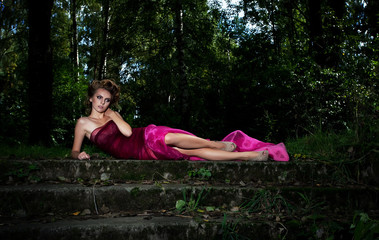 Evening scenic - lying pretty lady on staircase among trees
