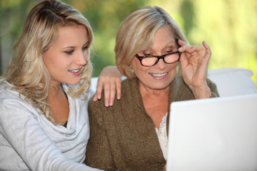 Mother and daughter sat with laptop