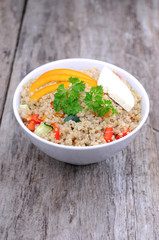 Vertical photo of quinoa salad on wooden background