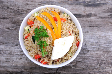Overhead view of bowl of quinoa salad with cheese and vegetables