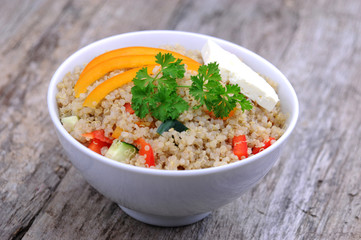 Bowl of quinoa salad with feta cheese and vegetables