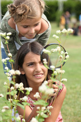 Little girls observing flowers through magnifying glass