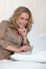 Smiling woman using her laptop on a white sofa