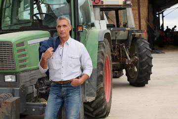 farmer posing near tractors