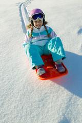 Happy winter - little girl  sledging downhill