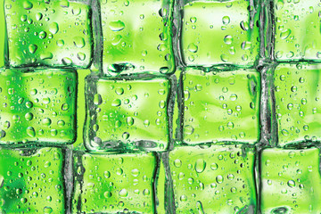 Melting ice cubes on green closeup
