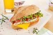 Chicken sandwich with fresh vegetables cheese.