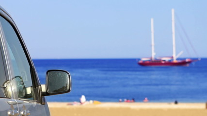 Coming to beach by car with sailing boat view