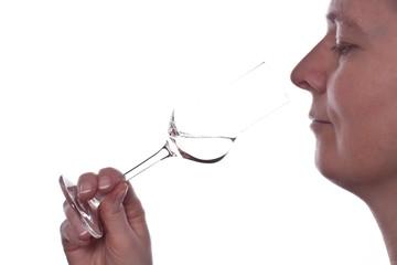 Frau riecht an einem Glas Grappa