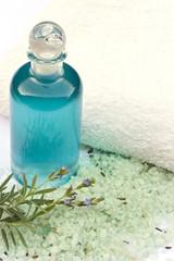 Lavendel, Öl in Flasche, Zweig mit Blüten vor Handtuch