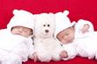 eineiige Zwillinge beim Mittagsschlaf mit Teddybär auf dem Sofa