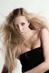Haare von junger Frau fliegen im Wind