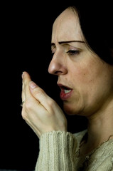 woman coughing, sneezing into hand