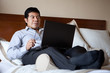Hispanic businessman using laptop in his hotel room