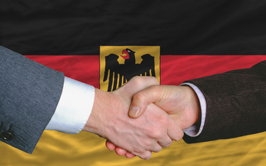 businessmen handshake after good deal in front of germany flag