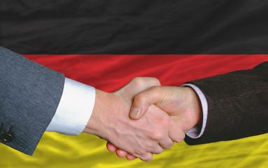 businessmen handshake after good deal in front of germany flag
