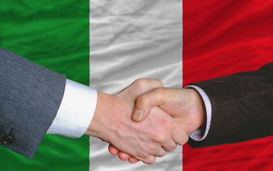 businessmen handshake after good deal in front of italy flag