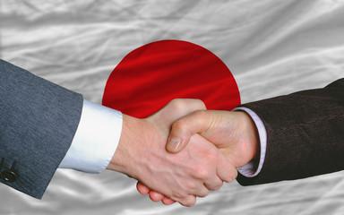 businessmen handshake after good deal in front of japan flag