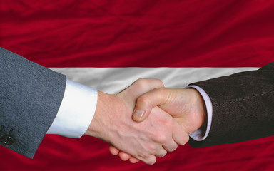 businessmen handshake after good deal in front of latvia flag